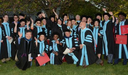 2019 doctoral grads and faculty in cap and gown cheering